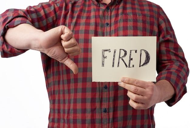 L'uomo in una camicia a quadri detiene un pezzo di carta con la scritta licenziata, concetto di disoccupazione sullo sfondo della crisi globale