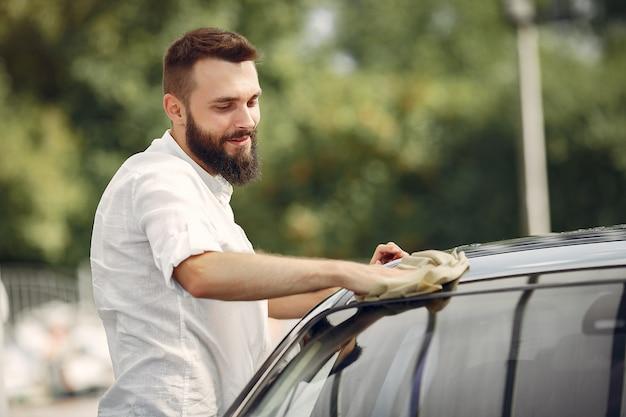 L'uomo in una camicia bianca pulisce un'auto in un autolavaggio