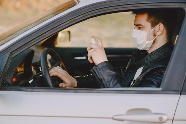 L'uomo in una maschera disinfetta la macchina