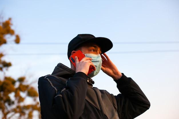 L'uomo in una mascherina medica tiene un telefono in mano, in piedi sulla strada. scoprire notizie, informazioni su un focolaio di influenza coronavirus