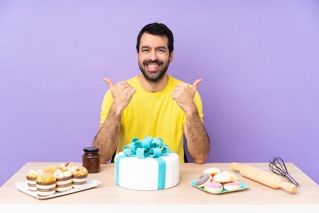 L'uomo in una tabella con una grande torta con i pollici aumenta il gesto e sorridere