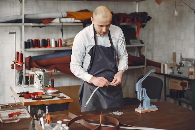 L'uomo in uno studio crea articoli in pelle
