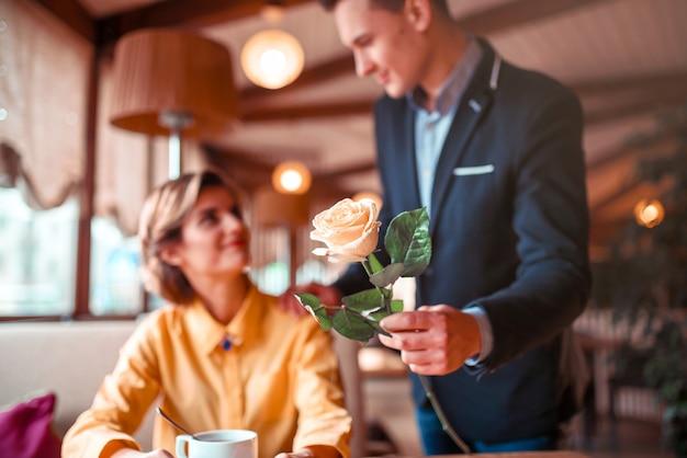 L'uomo in vestito dà fiore di rosa alla giovane donna felice, appuntamento romantico nel ristorante.