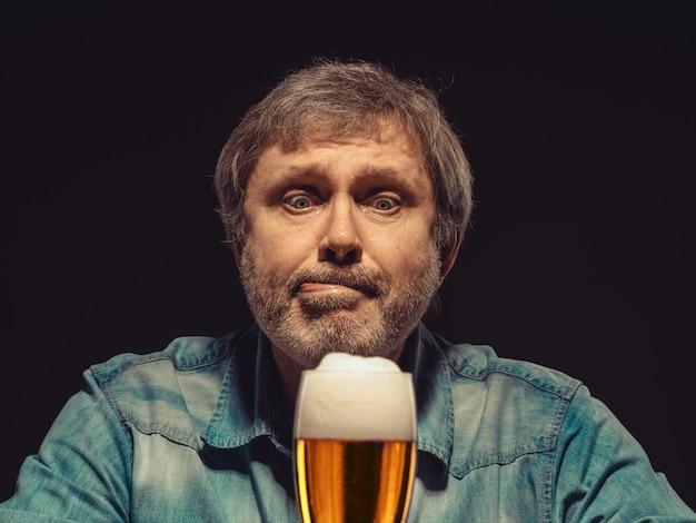 L'uomo incantato in camicia di jeans con un bicchiere di birra