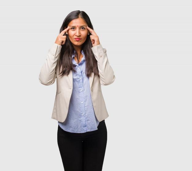 L'uomo indiano della giovane donna di affari che fa un gesto di concentrazione, guardando diritto ha messo a fuoco su un obiettivo