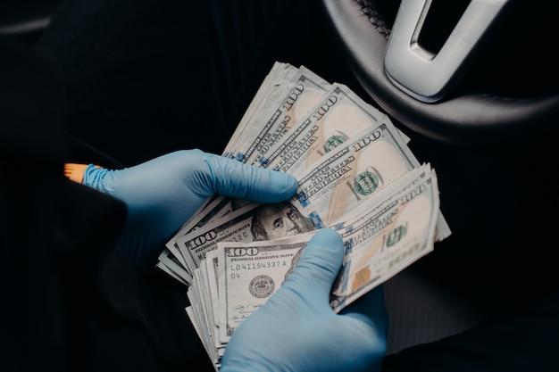 L'uomo indossa guanti protettivi medici, conta soldi sporchi, tiene banconote in dollari