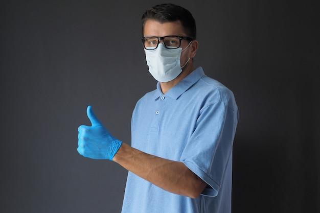 L'uomo indossa il guanto blu del lattice della maschera di protezione con il pollice sul gesto su fondo scuro.