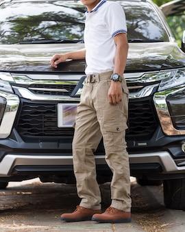 L'uomo indossa pantaloni cargo con parcheggio auto suv nel parco naturale