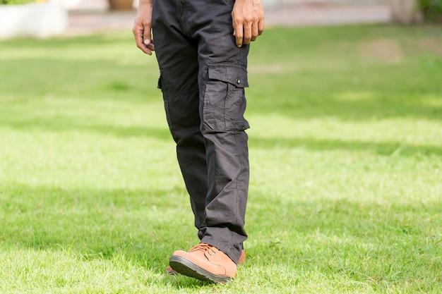 L'uomo indossa pantaloni cargo neri e in piedi nel parco naturale