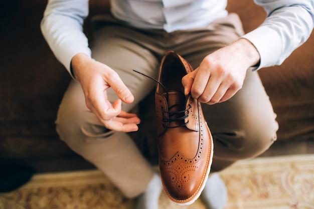 L'uomo indossa scarpe. lega i lacci sulle scarpe. stile maschile. professioni. prepararsi al lavoro, alla riunione.
