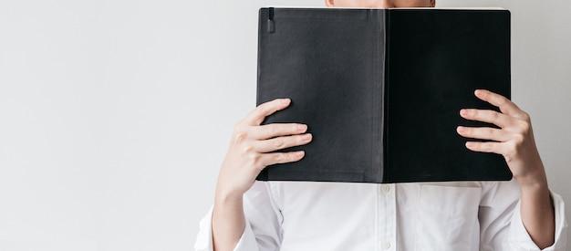 L'uomo indossa una camicia bianca e tiene in mano un libro di copertina nero.