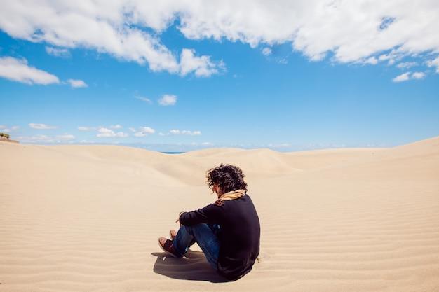 L'uomo irriconoscibile si siede su una duna del deserto. uomo che fa un giro turistico tra le dune in una calda giornata estiva.