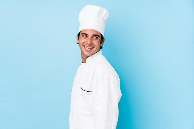 L'uomo isolato dei giovani cuoco guarda da parte sorridendo, allegro e piacevole.