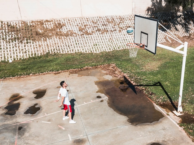 L'uomo lancia la pallacanestro nel canestro