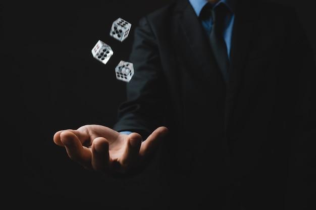 L'uomo lancia tre dadi con la mano, il concetto di gioco d'azzardo