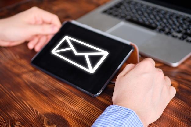 L'uomo lavora per il tablet e ha ricevuto un'e-mail.