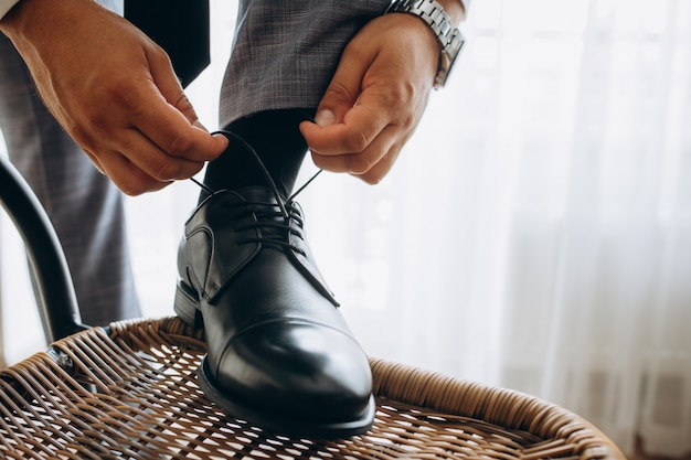 L'uomo lega le sue nuove lucenti scarpe da lavoro in pelle nera