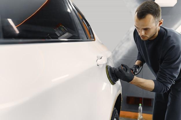 L'uomo lucidare un'auto in un garage