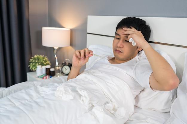 L'uomo malato è mal di testa e usa il termometro per controllare la sua temperatura a letto