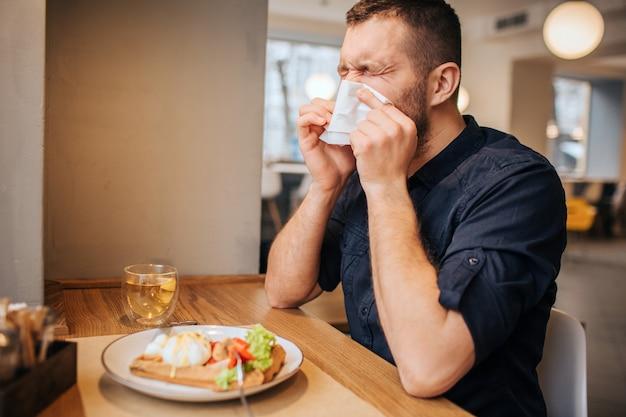 L'uomo malato è seduto al tavolo e starnutisce. si copre il naso con un tovagliolo bianco e tiene gli occhi chiusi. l'uomo è molto malato.
