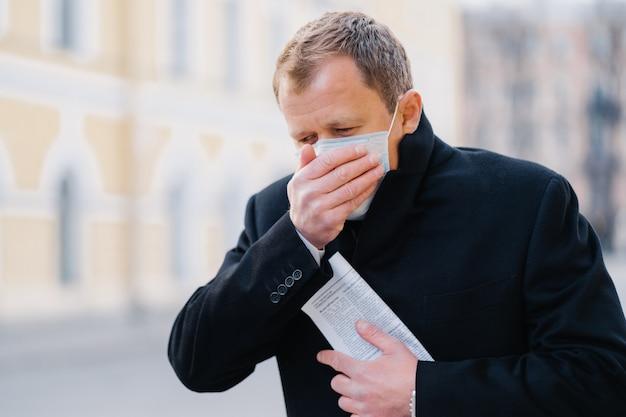 L'uomo malato tossisce, copre la bocca con il palmo, indossa una maschera medica, ha sintomi di allergia, influenza, influenza o coronavirus, cammina all'aperto, tiene il giornale, si sente male. covid-19, concetto di quarantena