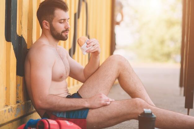 L'uomo mangia un hamburger dopo un allenamento. cibo molto affamato, grasso e malsano.