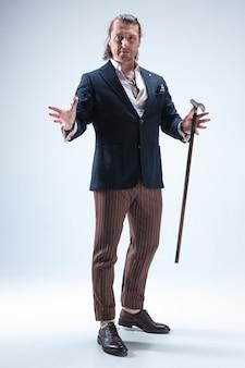 L'uomo maturo bardato in un vestito che tiene il bastone.
