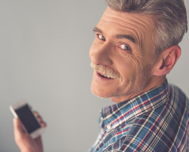 L'uomo maturo bello sta usando uno smart phone.