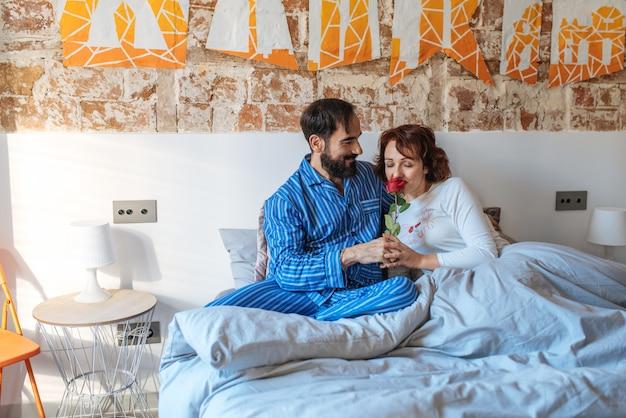 L'uomo maturo sul suo pigiama che dà una rosa il giorno di biglietti di s. valentino a sua moglie si è rilassato a casa a letto