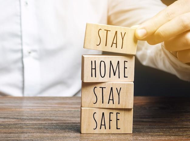 L'uomo mette blocchi di legno con le parole resta a casa, stai al sicuro. il concetto di prevenzione dal coronavirus