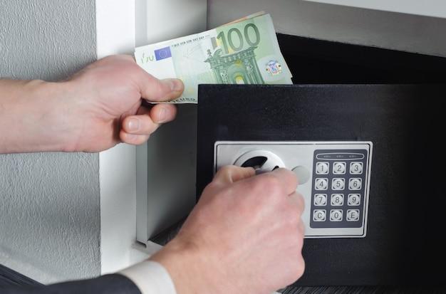 L'uomo mette i soldi nella cassaforte