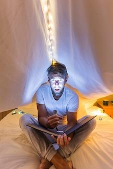 L'uomo mette in evidenza il suo volto con la torcia elettrica seduto sotto la tenda sul letto che tiene l'album