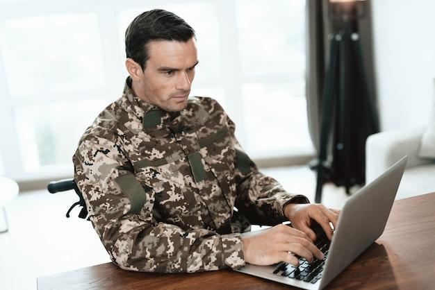 L'uomo militare bello lavora alla tabella sul computer portatile