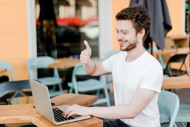 L'uomo mostra i pollici fino alla webcam del laptop