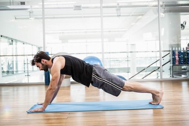 L'uomo muscolare che fa spinge verso l'alto sul tappeto in studio