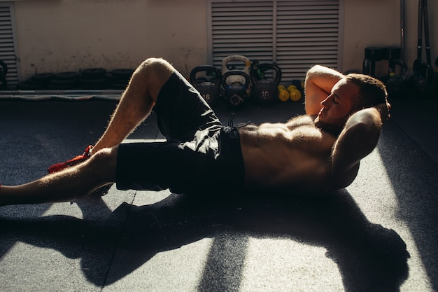 L'uomo muscolare che si esercita facendo si siede sull'esercizio