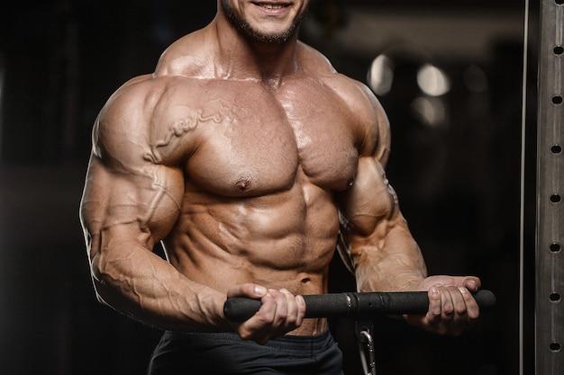 L'uomo muscolare di forma fisica del culturista che fa l'abs si esercita in palestra