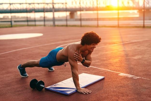 L'uomo muscolare senza camicia che fa la forza si esercita nella corte di mattina.