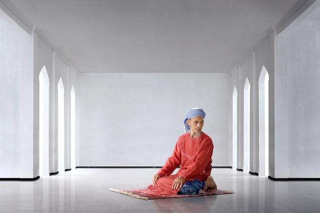 L'uomo musulmano asiatico anziano prega per dio