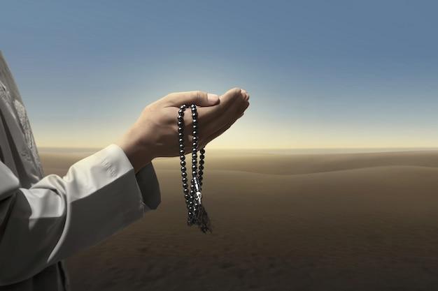 L'uomo musulmano prega con perline di preghiera