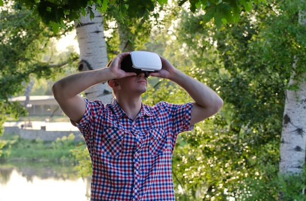 L'uomo nel casco della realtà virtuale contro lo spazio della natura