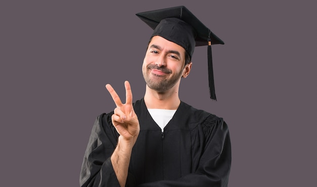 L'uomo nel suo giorno di laurea università felice e contando due con le dita su sfondo viola