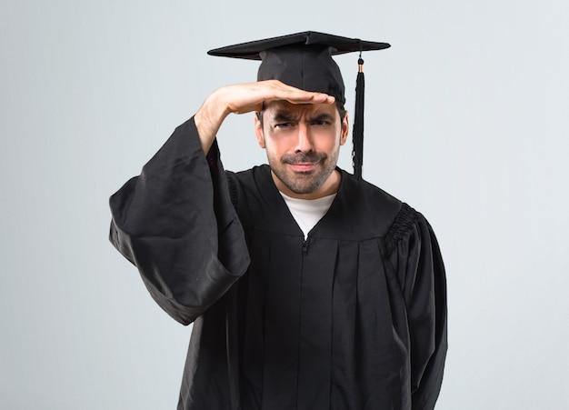 L'uomo nel suo giorno di laurea università guardando lontano con la mano per guardare qualcosa su sfondo grigio