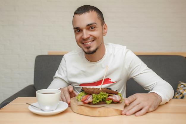 L'uomo nella caffetteria mangia un panino