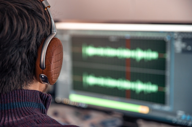 L'uomo nello studio fotografico registra e modifica il canto, la voce e la musica per uso commerciale. funziona in un editor audio in un computer con cuffie