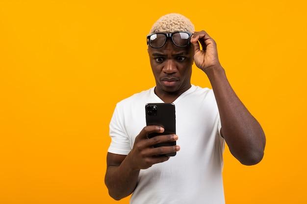 L'uomo nero africano bello sembra sorpreso sul telefono su giallo