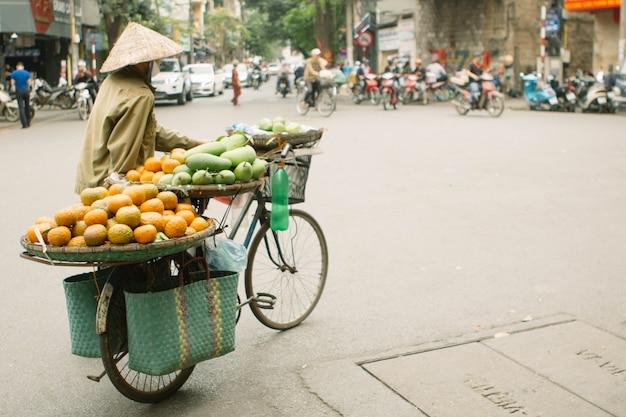 L'uomo non identificato guida una bicicletta con i canestri a hanoi, vietnam. la vendita ambulante in bicicletta è una parte essenziale della vita in vietnam