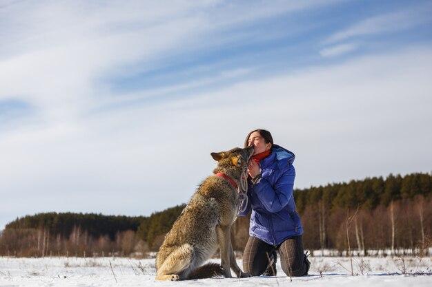 L'uomo nutre i suoi biscotti per cani husky di bocca in bocca all'aperto