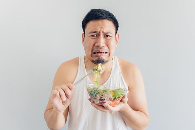 L'uomo odia il pasto sano dell'insalata.