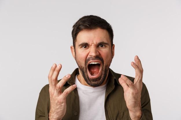 L'uomo perde la pazienza sentendo aggressività e depressione. maschio barbuto angosciato e infastidito, stufo di litigare, gridare, stringere la mano aggressivo e maledire qualcuno, sembrare arrabbiato